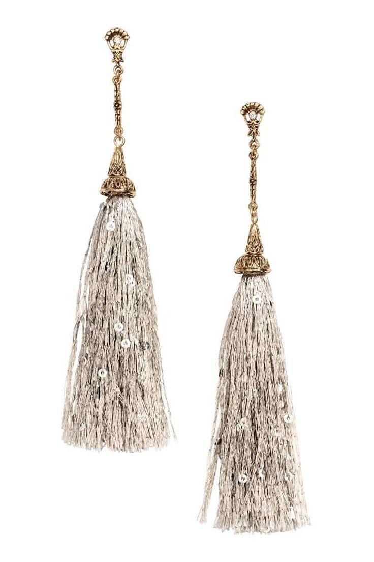 Lange Ohrringe mit Quasten: Lange Ohrhänger aus geprägtem Metall mit paillettenbesetzten Quasten. Länge 13 cm.