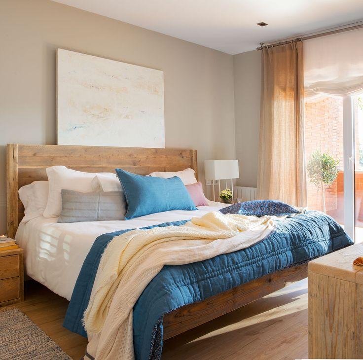 En la cama Cama de madera reciclada de Sacum. Edredón azul y cojines de Filocolore.