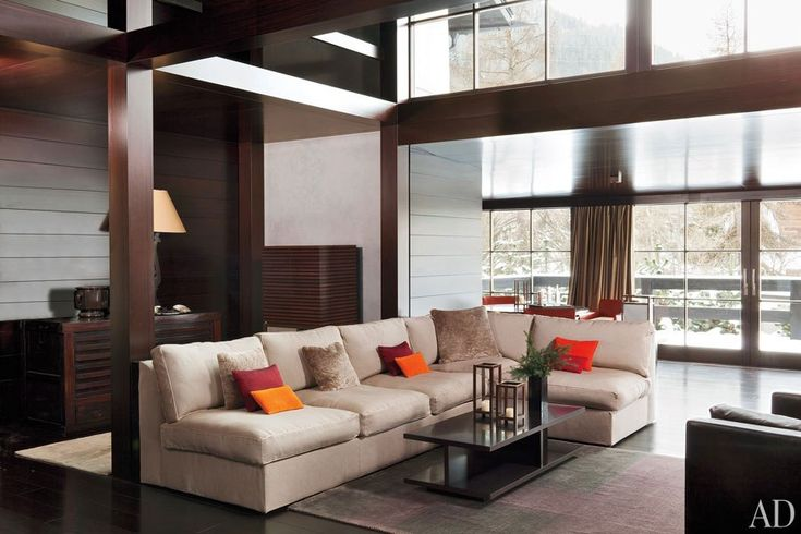 The couturier and his design team adapted a 17th-century barn into a high-ceilinged living room with a glass curtain wall looking out to the Alps. The sofa, cocktail table, and silk rug are by Armani/Casa.