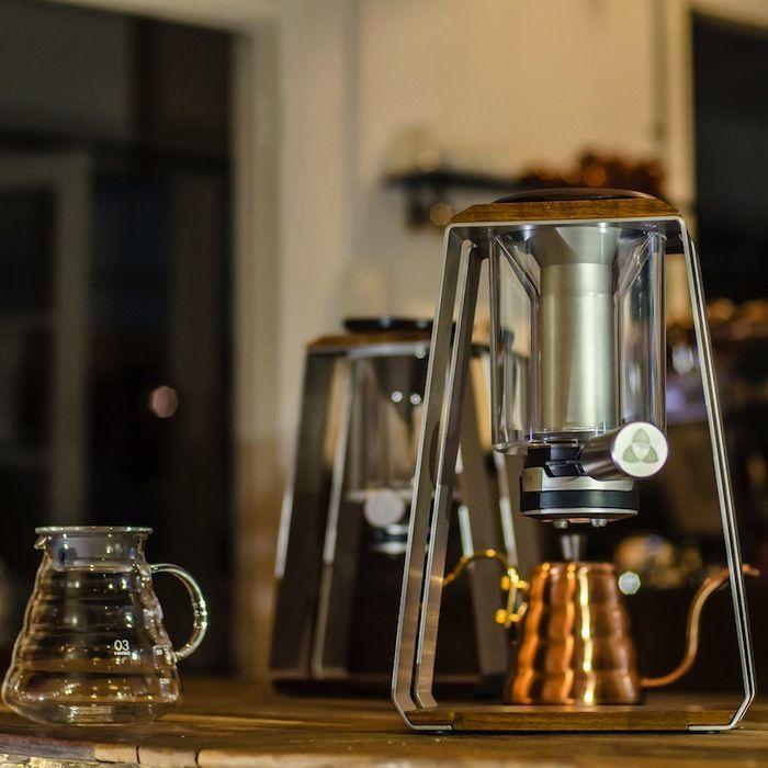 TRINITY COFEEが製作した自動エアプレス機つきコーヒーメーカーTRINITY ONE COFEE BREWER。ブラックウォルナットとステンレスで作られたワイヤーが中央のシリンダーを支えるミニマムなデザイン。ドリップコーヒーもエスプレッソもアイスコーヒーも楽しめちゃう。