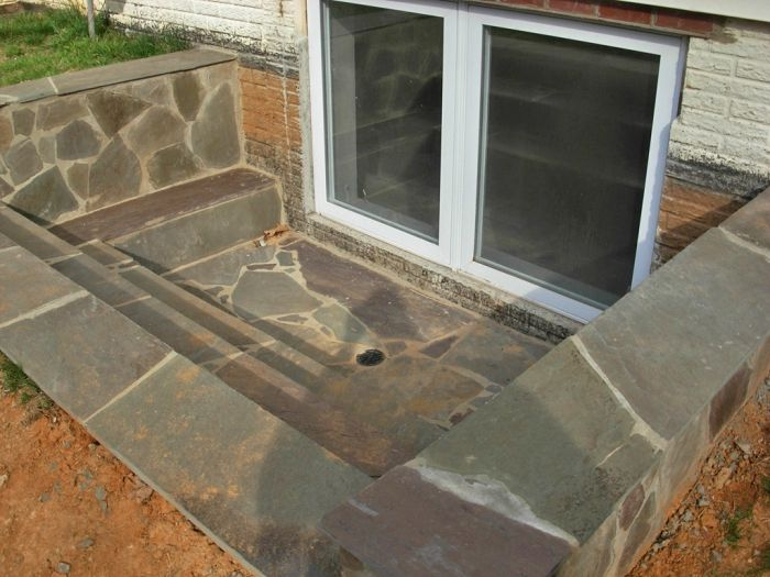 stone steps leading to basement egress window