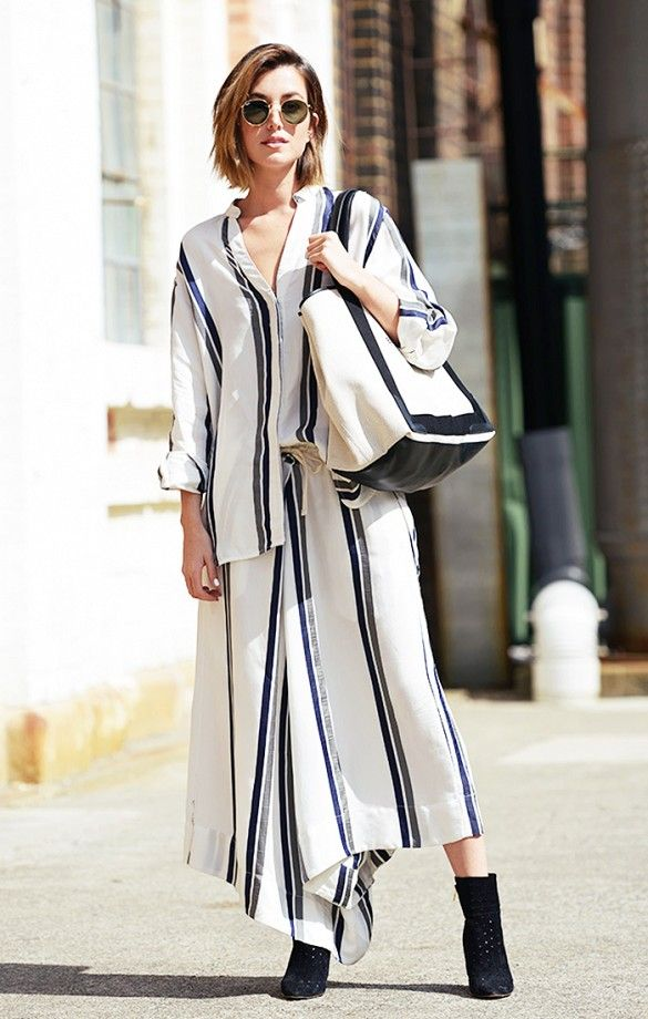 An oversized striped top is worn with matching striped bottoms, black booties, an oversized tote bag and circle sunglasses.