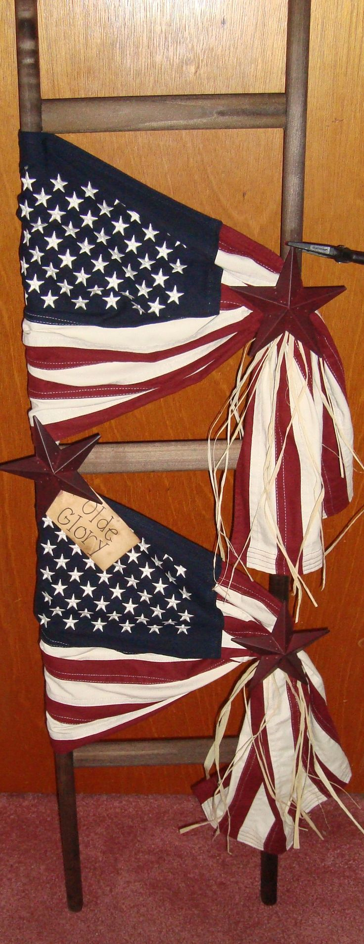 4 foot rustic wooden ladder with two Americana flags accented with raffia and stars. $48.00