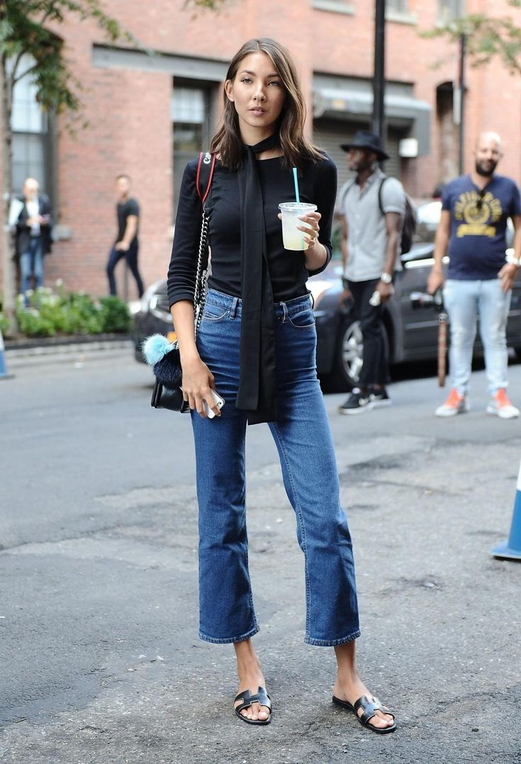 Cropped flared denim with a black top, skinny scarf, and leather sandals.