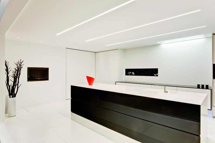 Subtle colour accents in a clean white kitchen. Lighting by TAL: 2U recessed profile system.