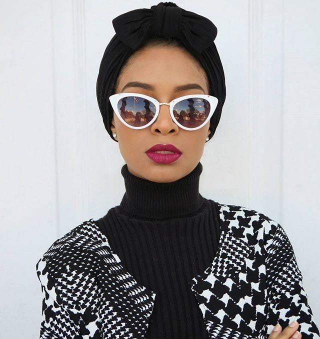 B&W faux houndstooth cardigan over black broad-wale corduroy turtleneck, magenta lips, teardrop white-framed eyeshades, black turban