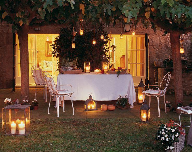 Mesa de comedor bajo árboles, rodeada de farolillos 00293576