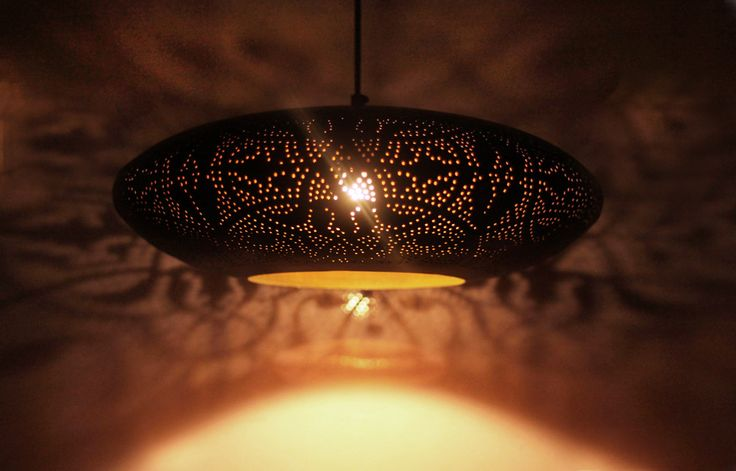 Ufo vormige lamp met licht en schaduw patronen projectie op muur en plafond.