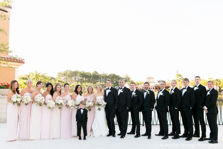 a classic and traditional wedding party of bridesmaids in full length blush gowns and men in black tuxedos.