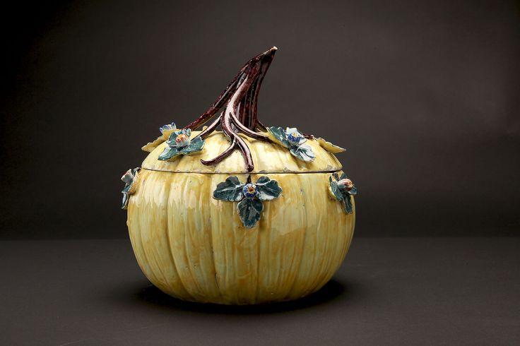 """Dutch Delft polychrome pumpkin tureen, Hendrik Van Hoorn, De Drie Posteleyne Atonne"""", 1759-1804 Diam.: 25 cm Amusante terrine en """"trompe l'œil"""" adoptant la forme d'une courge. Elle est décorée au naturel avec des émaux dits """"de grand feu"""". La couleur jaune est obtenue grâce à l'oxyde d'antimoine, la couleur verte des feuilles provient de l'oxyde de cuivre, le brun violacé de la queue et des branches trouve son origine dans l'oxyde de manganèse et la teinte rouge rehaussant les boutons de…"""