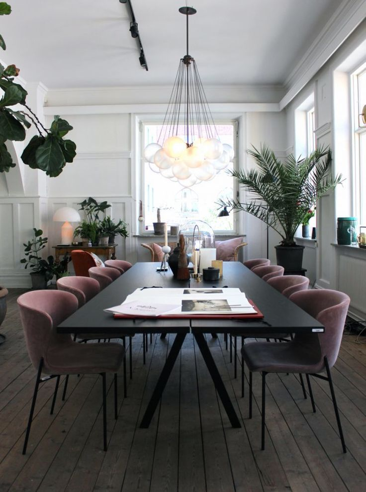 In the dining room, a Solid Wood Saw Table from Friends & Founders is surrounded by a suite of pink velvet upholstered dining chairs. The Cloud 19 Pendant Lamp by NYC designers Apparatus hovers overhead.