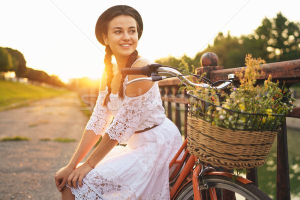 Young beautiful woman sitting on her bicycle with flowers at sun stock photo (c) vlad_star (#8665338) | Stockfresh
