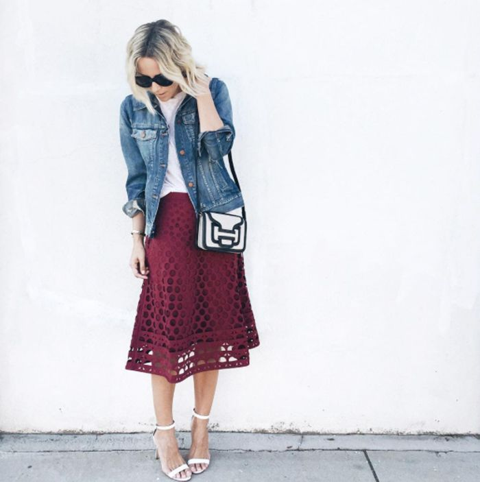 Jacey Duprie of Damsel in Dior wears a knee-length red skirt with a white t-shirt, a denim jacket, white sandals, black sunglasses, and a black and white crossbody bag