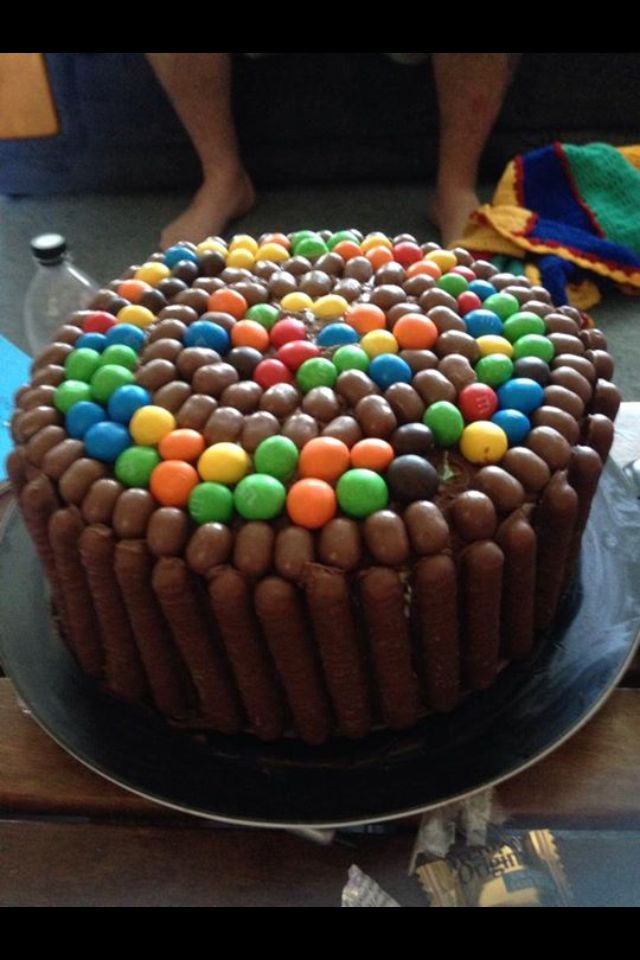 Little brothers 12th birthday . Vanilla sponge layer cake .filled with cream and jam. Choc & yogurt icing. Cadbury fingers,mnm's and marvellous creations choc covered jelly beans