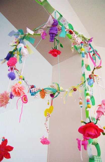 bright and cheerful mobile made from colorful ribbons, toys, flowers, etc.
