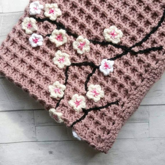 Dusky pink crochet blanket in attractive waffle stitch with small fishnet border. Crocheted in dusty pink Aran weight yarn, this stitch makes a thick and luxurious feeling blanket. Features floral embellishments designed to evoke cherry blossoms in complimentary whites and creams with pink centres over black chain stitched branches. Measures - 87cm x 6270cm (34 x 27.5), so a good size for a lap blanket, pram blanket, baby blanket, or small throw to protect the back of a sofa or armchair. It…