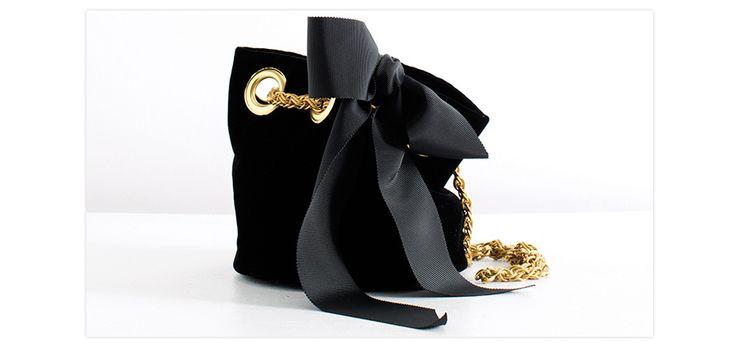 En velours noir ponctué de touches d'or, voici une version grand soir du fameux modèle seau de la créatrice parisienne. Le tout orné d'un délicat nœud en satin de poudre,
