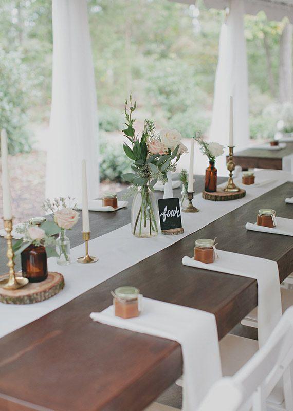 Table de mariage rustique chic - xit la nappe sur la table de mariage, ce chemin de table blanc immaculé est du plus bel effet posé directement sur le bois sombre de cette table. Les ingrédients pour que cette magie rustique chic opère : Quelques bougeoirs en laiton et bouquets de fleurs posés sur des rondins de bois en guise de dessous de plat, des bouts d'ardoise pour numéroter les tables...