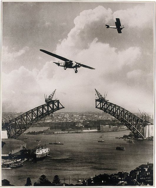 "Sydney Harbour Bridge during construction, 1930, with two aeroplanes, Charles Ulm's ""Southern Sun"" & a Gypsy Moth / photomontage by Edward Searl"