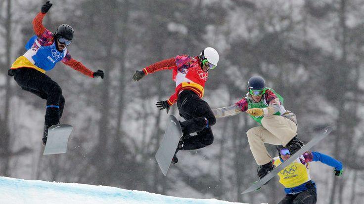 Regino Hernandez of Spain (blue bib), Lucas Eguibar of Spain (red bib), Alex Deibold of the United States (green bib) and Lluis Marin Tarroch of Andorra (yellow bib) compete in the men's snowboard cross 1/8 finals.