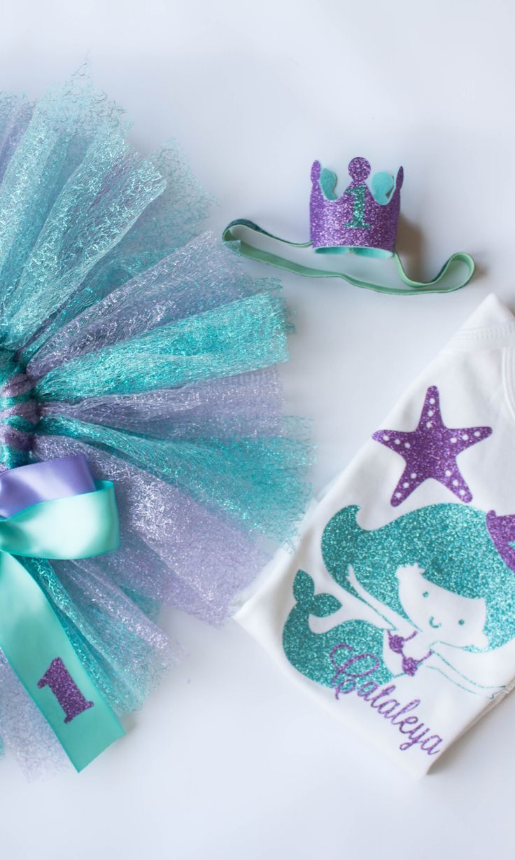 Birthday mermaid party tutu outfit for little baby girls in aqua teal and lavender purple. Glittery, sparkly, personalized! Perfect as a first birthday cake smash outfit idea for photos and party.  Includes tutu, shirt, and party crown on an elastic headband! Sparkly tutu looks like a beautiful mermaid tail!
