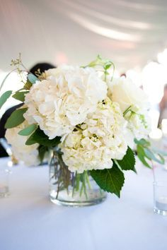 the simple centerpiece of hydrangea with minimal greenery added in a low cylinder.