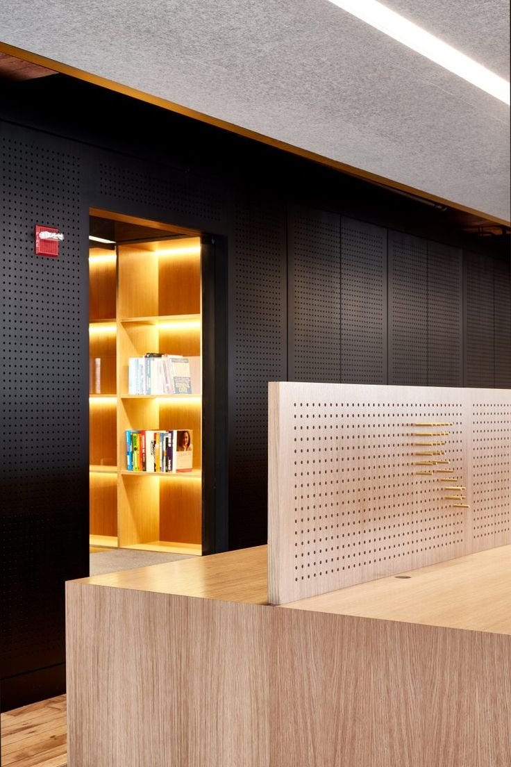 "Oak plywood walls are stained black and pierced with hundreds of thousands of holes in this office. ""The peg holes enable staff to utilise the entire surface in myriad of ways,"" said the firm."