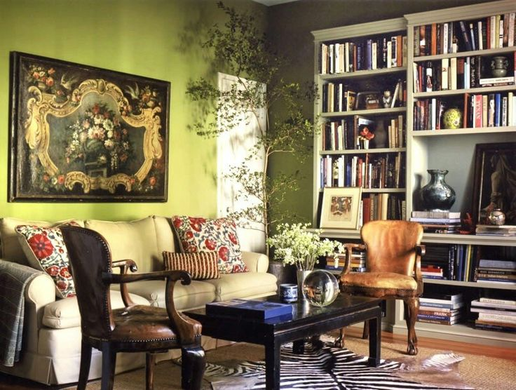 Eclectic, intellectual bohemian style living room... The green wall combined with the bookshelves and zebra print rug, anchored by the more traditional style furniture, makes it feel as if your college English Lit Professor would call this home