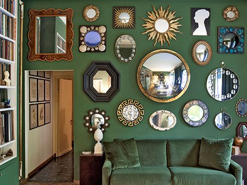 Hankering for loads of glamour on the cheap? This cache of small-scale 1950s looking glasses adds up to one majorly sparkling focal point. The dark-green paint and matching velvet settee practically fade into the background, while the loose symmetry creates an orderly, knockout effect.