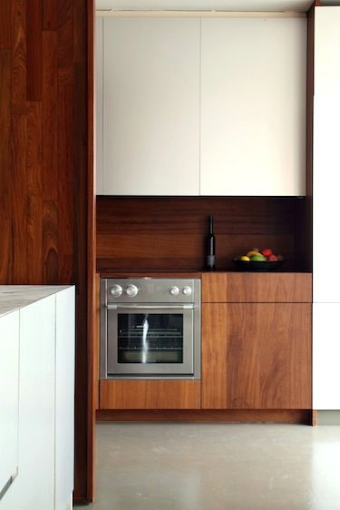 Modern kitchen w/ white and wood slab cabinets | Get this look with Northern Contours: Plain Sliced Black Walnut slabs, grain matched, pair with Ivory or Smoke Acrylic or