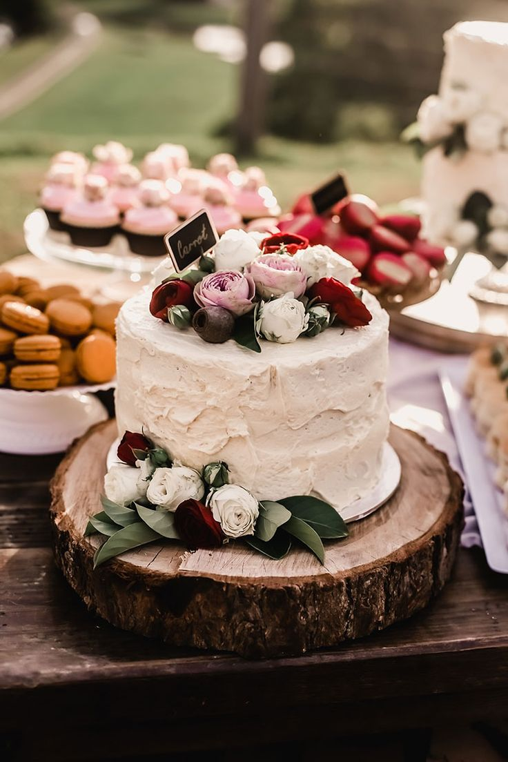 Rustic buttercream wedding cake with pink, red and white roses on a wood round | Emily Stone Fine Art Portraiture | See more: http://theweddingplaybook.com/vibrant-heartfelt-bohemian-wedding/