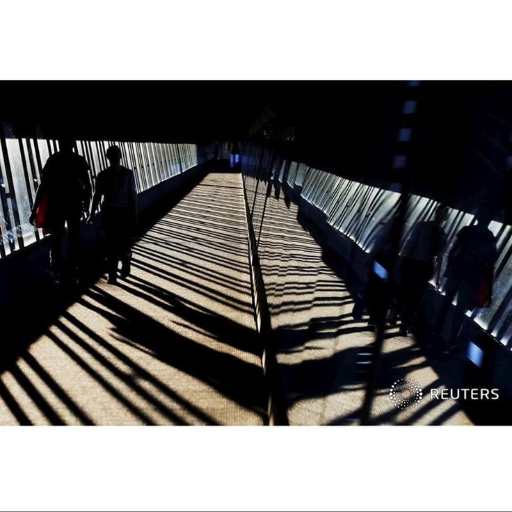 Commuters cross a skybridge linking a subway stop and a parking garage in the late afternoon in Medford Massachusetts October 6 2015.  REUTERS/Brian Snyder #Medford #massachusetts #bridge #shadow #picoftheday #commute by reuters