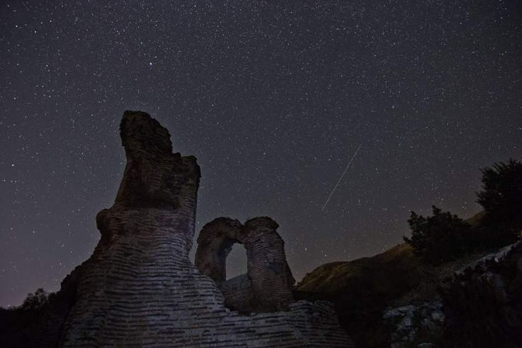A long exposure image shows a Perseid meteor streak across the night sky over the remains of St. Ilia Roman Christian basilica near the town of Pirdop on Aug. 12, 2015.
