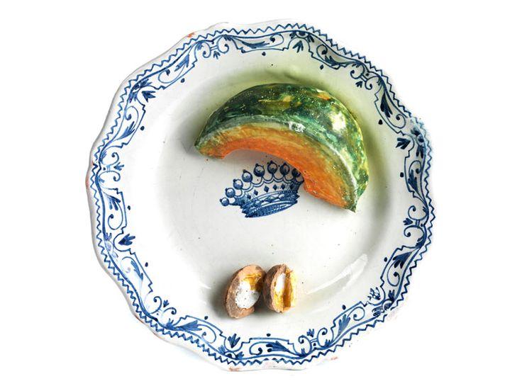 """piatto con pezzi di anguria a fette e gusci di noce aperti. LACHAPELLE Diametro:. 24 cm  In fondo in blu """"Lachapelle"""". Nella corona specchio nove punte in blu."""
