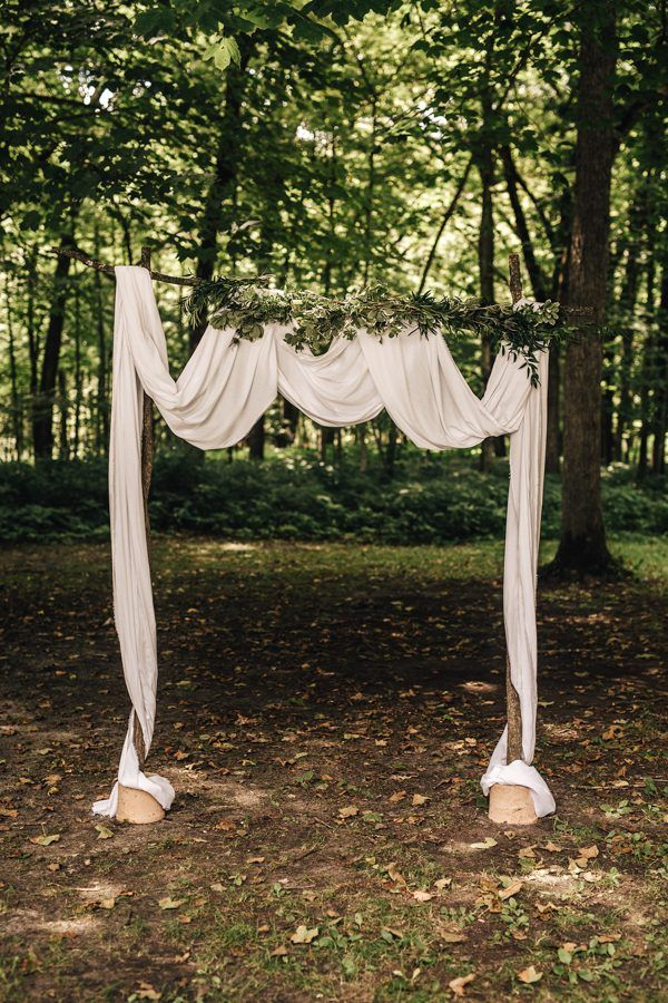 White fabric draped wedding ceremony arch | Image by Eastlyn Bright