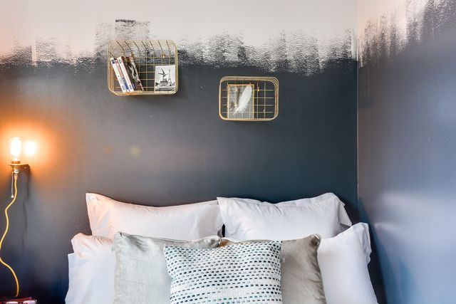 La décoratrice a choisi de la peinture noire et des étagères dorées pour habiller la tête de lit dans la deuxième chambre de l'appartement.