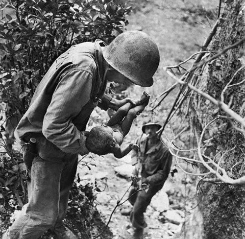 A US Marine saving a Japanese baby whose parents had committed suicide during the Battle of Saipan. Originally left for dead, the baby was found among a large pile of people who had killed themselves.  June, 1944 - Saipan.