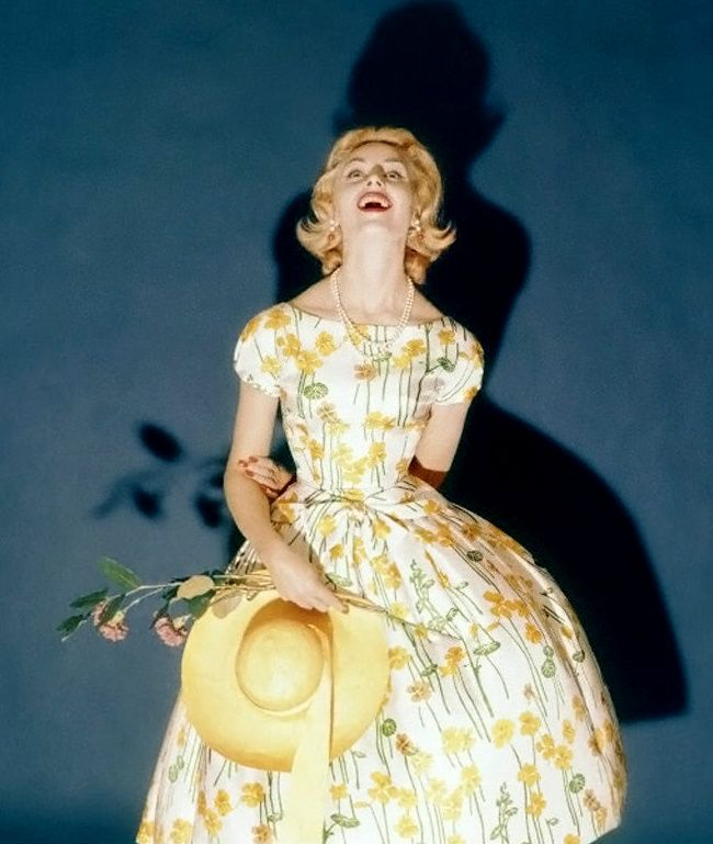 1958 Model wearing party dress with nasturtium print on white background by Kasper of Arnold & Fox, and a straw hat by John Frederics Charmer