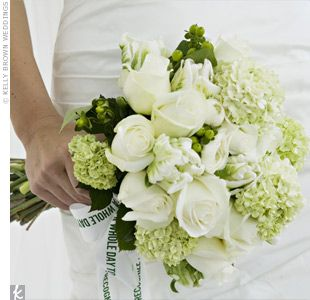 "Viburnum, parrot tulips, ranunculus, roses, hypericum berries, and camellia in white and green were wrapped with a ribbon printed with the couple's wedding quote: ""Don't take a whole day to recognize sunshine."""