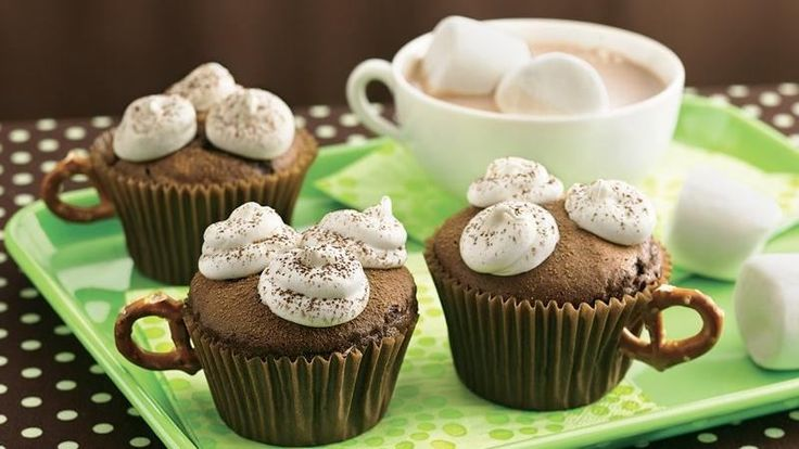 """Vanilla frosting """"marshmallows"""" are piped onto devil's food cupcakes to mimic the look of a favorite hot drink. Don't forget the pretzel """"cup handles""""!"""