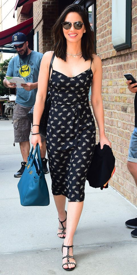 We can't get over Olivia Munn's summer look. The actress stepped out in New York City wearing a flirty black floral dress with a charming tie around the waist. Munn accessorized with a pair of metallic sandals, delicate necklaces, round shades, and a blue leather Hermès bag.