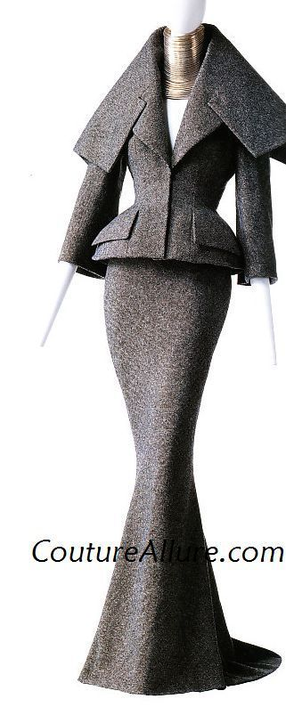 John Galliano for Christian Dior Haute Couture, Autumn 1997 two piece suit of gray wool tweed. The jacket peplum is padded and references the jackets of Dior's New Look of 1947. Worn with a choker made of 35 rings of silver. From the collection of the KCI.