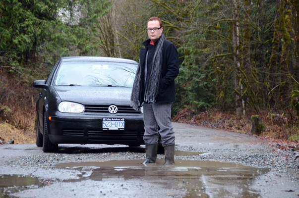 Bradley Gionet stands in one of the many potholes that make a trip down the forest service road to his family home treacherous.
