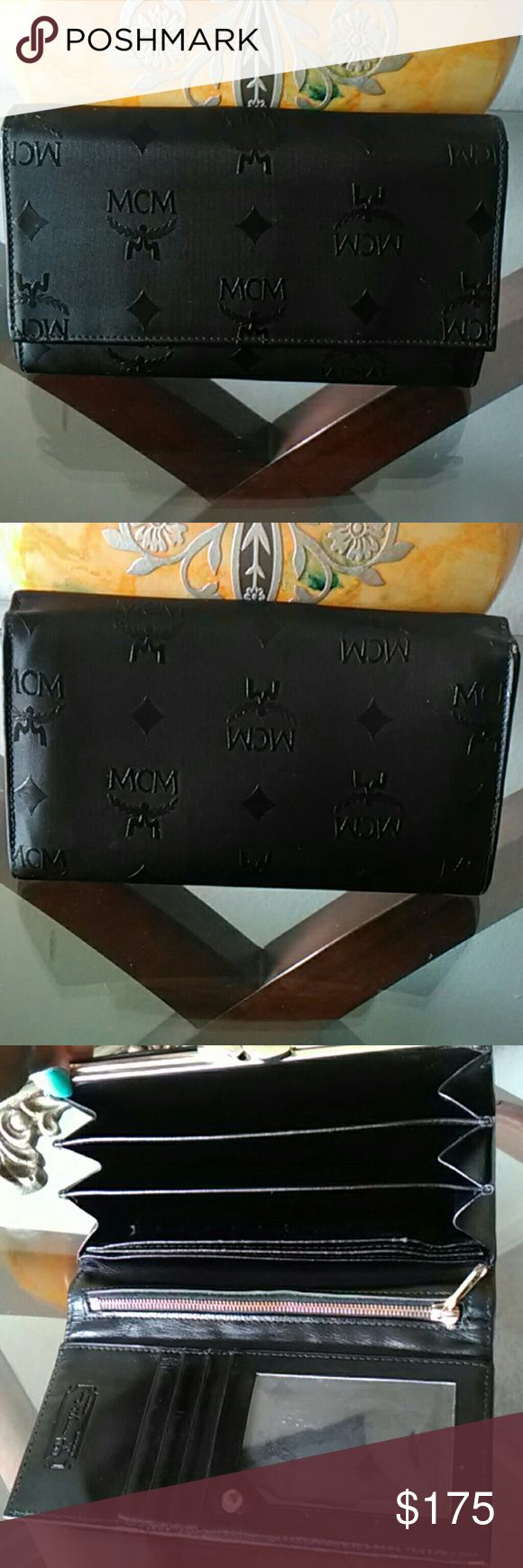 MCM Authentic Black Long Wallet Good preowned condition. Minor scuff around edges and peeling inside checkbook insert compartment. Numerous compartments for bills, and receipts. Kiss lock coin pocket and zipper pocket. MCM Bags Wallets