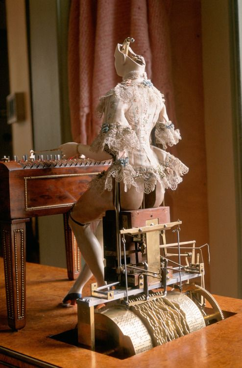 The Queen's Android  Marie-Antoinette's dulcimer player, forerunner of the robot.  Date: 1784, Paris, musée des Arts et Métiers  This famous android was a collaborative effort by two Germans. Clockmaker Peter Kintzing created the mechanism and joiner David Roentgen crafted the cabinet; the dress dates from the 19th century. Automatons were in circulation and aroused much curiosity.