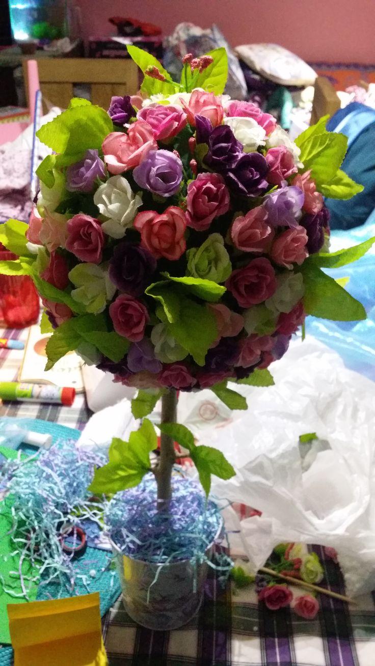 Arbolito hecho de esfera de plumavit con flores. El tallo es una rama de árbol seco en un balde floreado