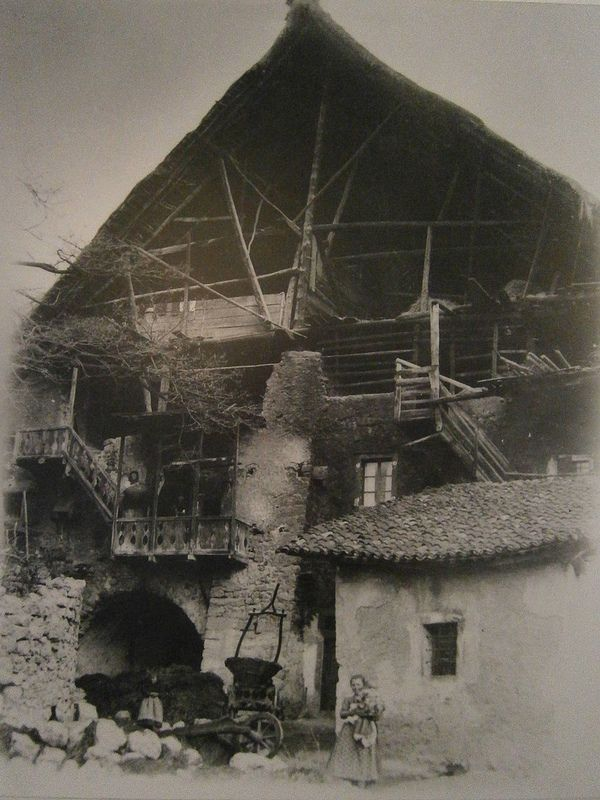 """Characteristic houses of an Italian mountain village - Woman holding a child outside the house of Grigoi in """"Piazza di Sotto"""" (the lower square) in Stenico, Italy, with balconies and """"soleri"""" (open attics) and a thatched roof. Note the walls stained with smoke, after the 1909 fire.    #TuscanyAgriturismoGiratola"""