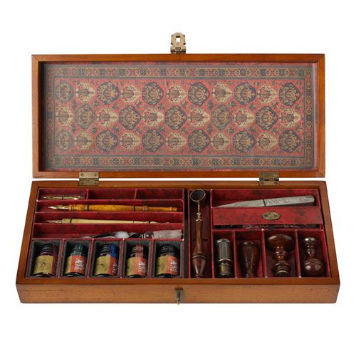 BRITISH MUSEUM - Trianon Letters Calligraphy Set (£140). Beautiful French finish honey wood box lined with antique-patterned paper. 1 glass, 2 wood stylus, various brass nibs, 5 assorted inks in rich colours- Flamingo, Forest Rain, Starlit Sky, Burnt Sienna and Pitch Black, a brass melting spoon, three beautifully turned wood and brass seals, a miniature travel burner to melt the wax and a sealing wax bar.  Exhibition: Shakespeare Size: Length: 37cm. Width: 16cm. Height: 6.5cm., Weight…
