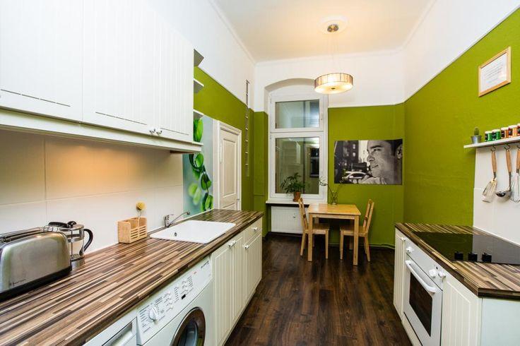 Modern eingerichtete Küche mit grüner Wandfarbe, dunklem Holzoden und weißen Fronten.  #interior #Berlin #kitchen