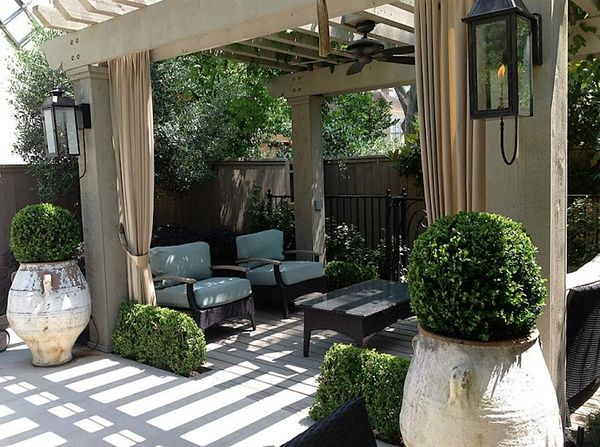 Adding lanterns and drapes and a fan...makes the wood pergola feel like an outdoor room.
